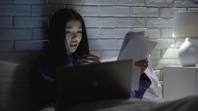 Азиатская женщина делая отчет в спальне вечером, надоеданный с работой, прогар работы сток-видео
