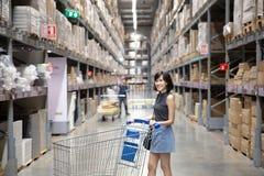 Азиатская женщина делая покупки и идя с ее тележкой в грузе или складе стоковое изображение