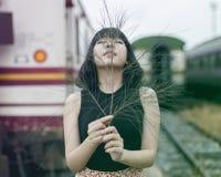 Азиатская женщина держа ветвь дерева показывать на вокзале стоковое изображение