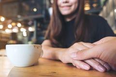 Азиатская женщина держа руку ` s человека с влюбленностью и warmness чувства стоковая фотография