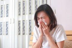Азиатская женщина дуя ее нос пока сидящ на кровати Женщина болезни Стоковые Фотографии RF