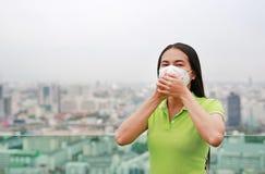 Азиатская женщина дыша путем носить маску защиты против премьер-министра 2 загрязнение воздуха 5 в городе Бангкока r стоковое фото rf