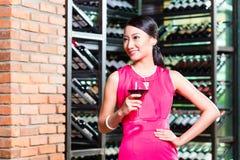 Азиатская женщина держа бокал вина стоковая фотография