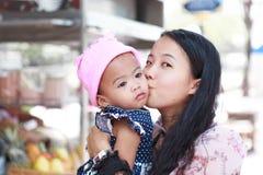 Азиатская женщина держа и целуя младенца Стоковые Изображения