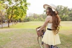 Азиатская женщина ехать велосипед Стоковая Фотография