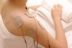 Азиатская женщина делает массаж электрического - стимулирование (десятки) Стоковая Фотография