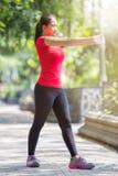 Азиатская женщина делая протягивающ тренировку во время внешнего перекрестного поезда Стоковые Изображения RF