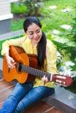 Азиатская женщина играя классическую гитару, внешнюю на дневном времени с бригом стоковые изображения rf