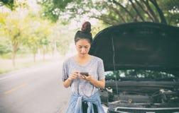 Азиатская женщина используя мобильный телефон пока смотрящ и усиленный человек si Стоковые Изображения