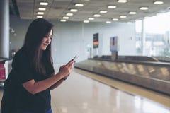 Азиатская женщина используя мобильный телефон с чувствовать сторона счастливых и smiley, положение и ждать заявка багажа в авиапо стоковое фото