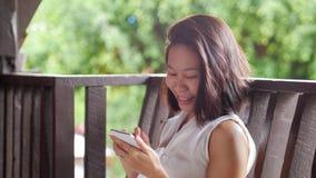 Азиатская женщина используя улыбку мобильного телефона счастливую в естественном саде природы Стоковые Фото