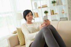 азиатская женщина используя smartphone дома Стоковое Изображение RF
