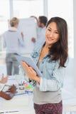 Азиатская женщина используя ее таблетку пока ее коллеги работают Стоковые Изображения