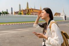 Азиатская женщина используя карту земли телефона онлайн Стоковое фото RF