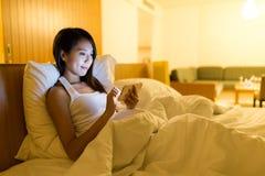 Азиатская женщина используя мобильный телефон дома Стоковые Фотографии RF