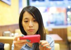 Азиатская женщина используя мобильный телефон принимает фото стоковые изображения rf