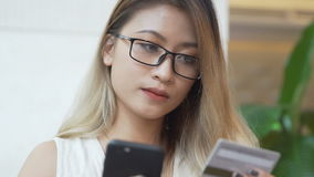 Азиатская женщина используя мобильный телефон для онлайн приобретения с кредитной карточкой акции видеоматериалы
