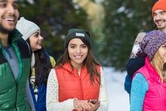 Азиатская женщина используя молодые люди зимы группы умного леса снега телефона счастливое усмехаясь идя внешней Стоковые Изображения RF