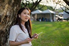 Азиатская женщина используя таблетку и слушающ к музыке Стоковые Фото