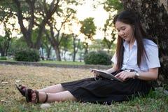 Азиатская женщина используя таблетку и слушающ к музыке Стоковое Фото