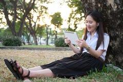 Азиатская женщина используя таблетку и слушающ к музыке Стоковое Изображение