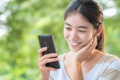 Азиатская женщина используя smartphone Стоковые Фотографии RF