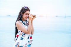 Азиатская женщина наслаждается принимает фото цифровой фотокамера на пляже одиночно Стоковые Изображения RF