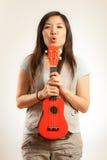 Азиатская женщина наслаждается гавайской гитарой Стоковые Изображения