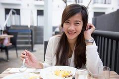 Азиатская женщина наслаждаясь ее обедом внешним Стоковая Фотография