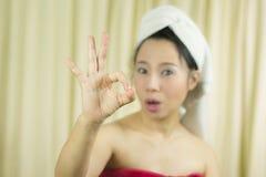 Азиатская женщина носит юбку для того чтобы покрыть ее грудь после волос мытья, в оболочке в полотенцах после ливня и давать знак стоковые фотографии rf