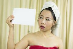 Азиатская женщина носит юбку для того чтобы покрыть ее грудь после волос мытья, в оболочке в полотенцах после ливня держа пустое  стоковое изображение