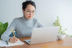 Азиатская женщина нося стекла использует офис ноутбука дома Студент портрета молодой милый работая на умном устройстве технологии стоковое изображение rf