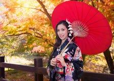 Азиатская женщина нося традиционное японское кимоно с красным зонтиком Стоковые Изображения