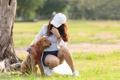 Азиатская женщина образа жизни играя с собакой приятельства золотого retriever в восходе солнца на открытом воздухе стоковые изображения rf