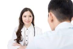 Азиатская женщина доктора говоря к человеку Стоковое Изображение