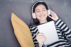 Азиатская женщина отдыхать, слушая к музыке на софе с наушником стоковые фото