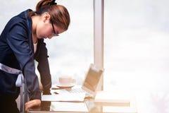 Азиатская женщина офиса стоя и держа рука на столе и смотреть Стоковое Изображение RF
