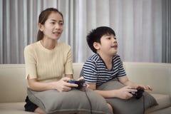 Азиатская женщина при азиатский мальчик играя видеоигры дома Стоковое фото RF