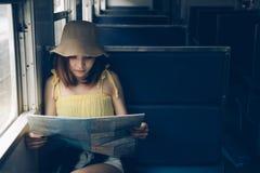 Азиатская женщина путешественника смотря карту на destinati находки вокзала Стоковая Фотография