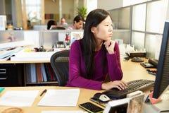 Азиатская женщина работая на компьютере в современном офисе Стоковые Изображения RF