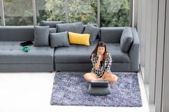 Азиатская женщина сидит на ковре пола с тетрадью и вызывать около s стоковые изображения