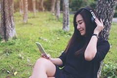 Азиатская женщина сидя и слушая к музыке с наушниками и держа умный телефон деревом с зеленой предпосылкой леса Стоковое Изображение RF