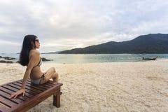 Азиатская женщина сидя на деревянном стуле на пляже стоковая фотография