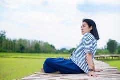 Азиатская женщина сидя перекрестная нога на бамбуковом мосте на поле риса на стоковая фотография