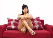 Азиатская женщина сидя на красной софе и смотря на камеру Стоковое Изображение RF