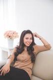 Азиатская женщина сидя на кресле Стоковая Фотография RF