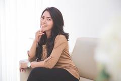 Азиатская женщина сидя на кресле Стоковые Изображения