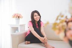 Азиатская женщина сидя на кресле Стоковые Изображения RF
