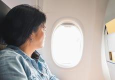 Азиатская женщина сидя на сиденье у окна в самолете и взгляде снаружи Стоковое Фото