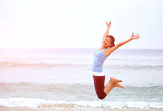 Азиатская женщина скача на пляж. Стоковые Фотографии RF